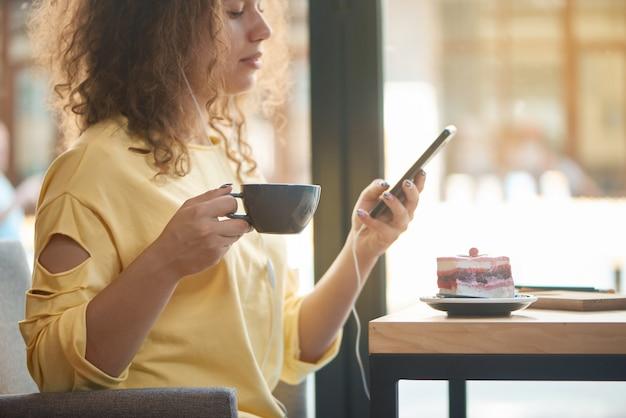 Geerntete seitenansicht des trinkenden kaffees des mädchens, musik im restaurant hörend.