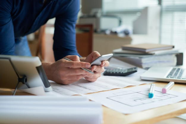 Geerntete unerkennbare person, die mit smartphone in den händen sich lehnen auf dem schreibtisch arbeitet