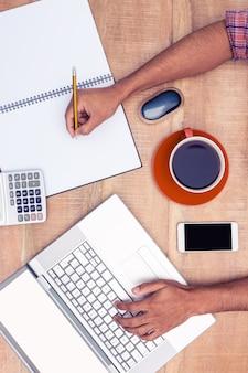 Geernteter geschäftsmann, der an laptop beim schreiben auf buch am schreibtisch im büro arbeitet