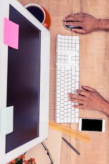 Geernteter handgeschäftsmann, der an computer am schreibtisch im büro arbeitet