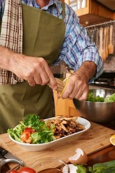 Geernteter männlicher koch, der zitronensaft dem teller hinzufügt