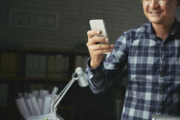 Geernteter mann, der das bewegliche app-lächeln verwendet
