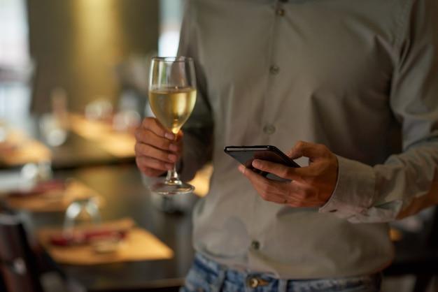 Geernteter mann, der das telefon hält sektkelch an einer party überprüft
