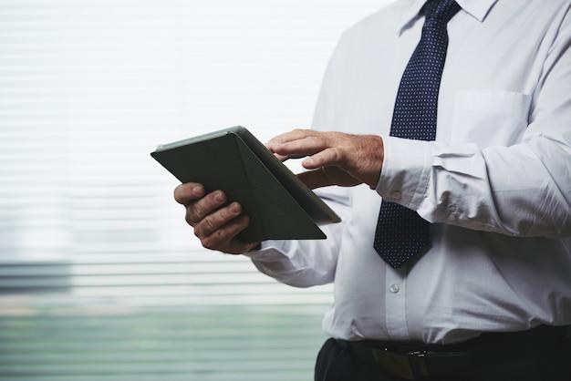 Geernteter mann, der geschäfts-app auf seinem tragbaren gerät verwendet