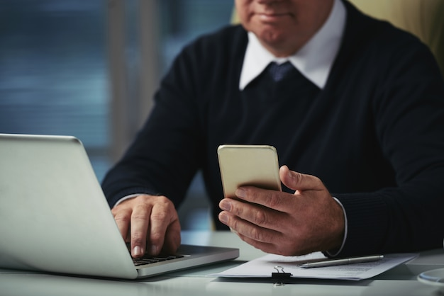 Geernteter mann, der mitteilungen an seinem telefon im büro überprüft