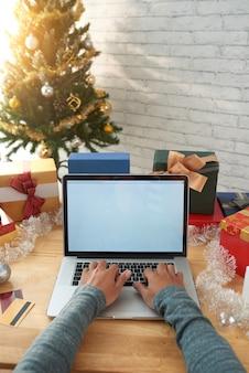 Geernteter mann, der onlinekäufe auf laptop vor weihnachten abschließt