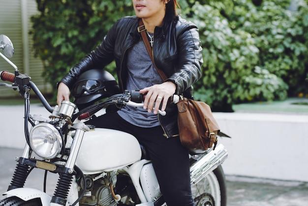 Geernteter radfahrer, der sein motorrad in der straße reitet