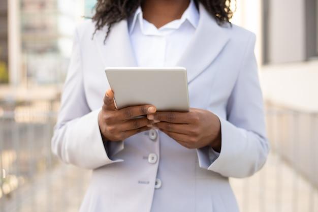 Geernteter schuss der afroamerikanergeschäftsfrau, die tablette verwendet. weibliche hände, die modernes digitales gerät halten. technologiekonzept