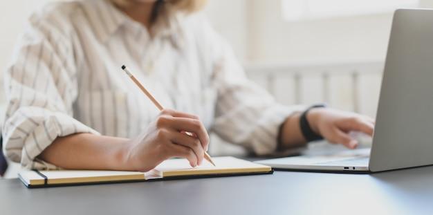 Geernteter schuss der jungen berufsgeschäftsfrau, die an ihrem projekt arbeitet und auf notizbuch schreibt
