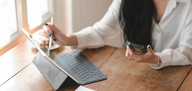 Geernteter schuss der jungen geschäftsfrau, die laptop-computer und smartphone beim arbeiten an ihrem projekt verwendet