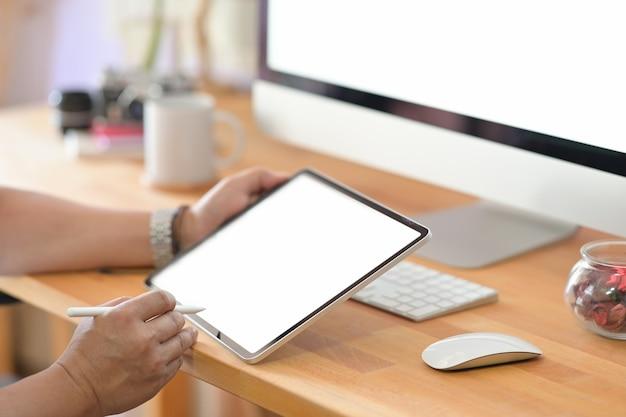 Geernteter schuss der männlichen handzeichnung am tragbaren tablet-computer am holztischstudioschreibtisch
