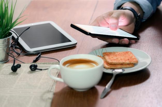 Geernteter schuss der mannhand unter verwendung des smartphone beim im café bei tisch sitzen.