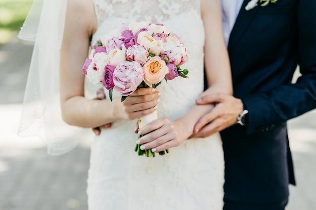 Geernteter schuss der schönen braut im weißen hochzeitskleid, das den blumenstrauß steht nahen bräutigam hält, der sie von hinten umarmt