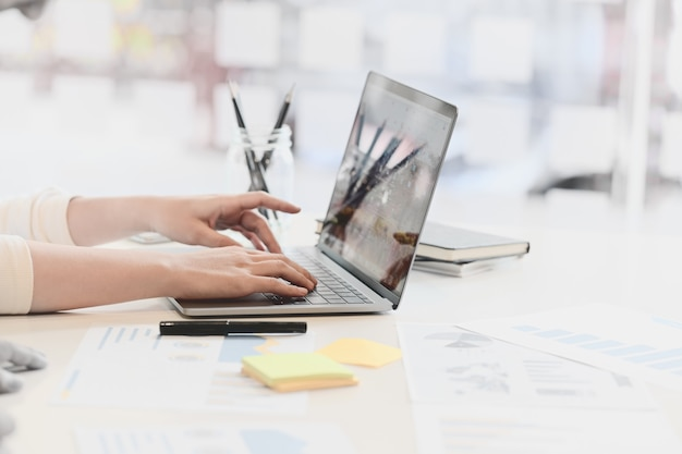 Geernteter schuss der weiblichen hand zu hause schreibend auf ihrem studioarbeitsplatz des laptops