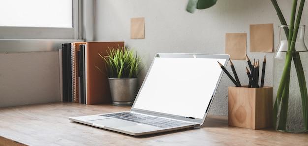 Geernteter schuss des bequemen arbeitsplatzes mit laptop-computer und büroartikeln des leeren bildschirms