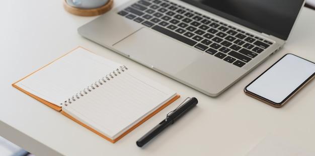 Geernteter schuss des bequemen arbeitsplatzes mit offenem notizbuch, laptop-computer und smartphone