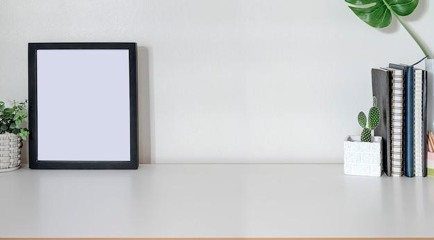 Geernteter schuss des bequemen arbeitsplatzes mit verspotten herauf rahmen, büroartikel und kopienraum auf weißer spitzentabelle.