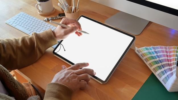 Geernteter schuss des designers, der grafiktablette beim arbeiten mit computer im studio oder im büro verwendet