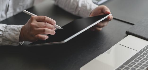 Geernteter schuss des erfolgreichen geschäftsmannes arbeitend an seinem projekt mit tablette