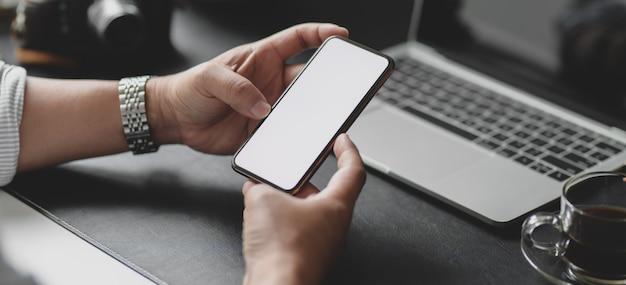 Geernteter schuss des geschäftsmannes smartphone des leeren bildschirms beim arbeiten an seinem projekt halten