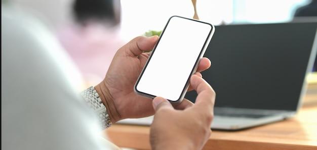 Geernteter schuss des geschäftsmannes smartphone des leeren bildschirms halten