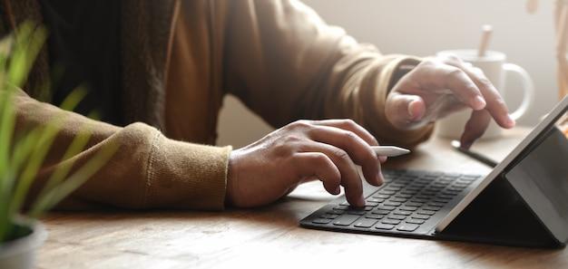 Geernteter schuss des jungen mannes arbeitend an seinem projekt bei der anwendung der tablette