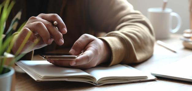 Geernteter schuss des jungen mannes arbeitend an seinem projekt bei der anwendung des smartphone