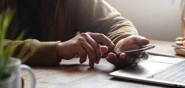 Geernteter schuss des jungen mannes, der seinen smartphone beim arbeiten an seinem projekt im bequemen büro verwendet