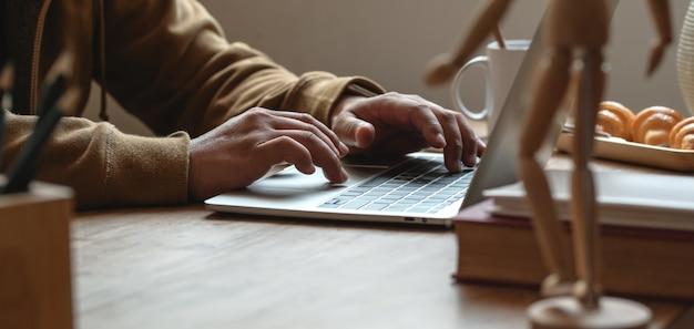 Geernteter schuss des jungen mannes schreibend auf laptop-computer an bequemem arbeitsplatz