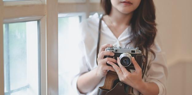 Geernteter schuss des jungen professionellen weiblichen fotografen, der weinlesekamera hält
