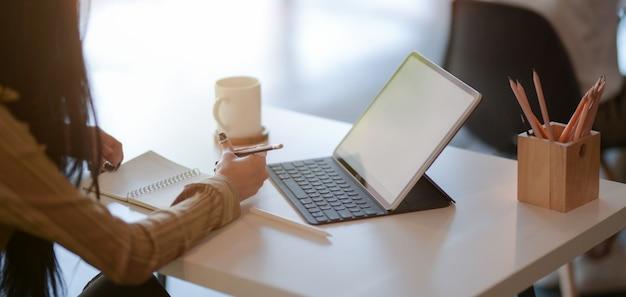 Geernteter schuss des jungen weiblichen designers, der ihr projekt mit digitaler tablette im modernen büro zeichnet