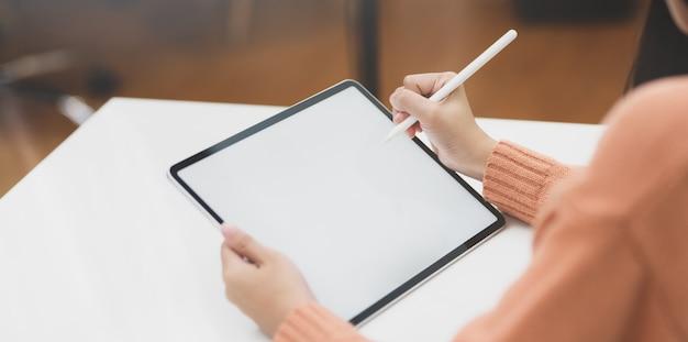 Geernteter schuss des jungen weiblichen freiberuflers, der an ihrem projekt beim redigieren auf tablette des leeren bildschirms arbeitet