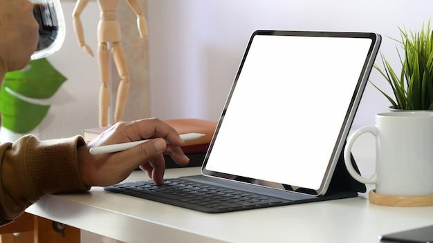 Geernteter schuss des mannes arbeitend an tablette und intelligenter tastatur im büro