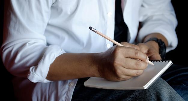 Geernteter schuss des mannschreibens auf papiernotizbuch mit bleistift