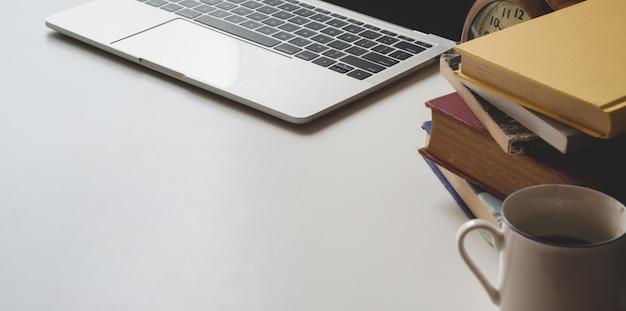 Geernteter schuss des modernen arbeitsplatzes mit laptop-computer und büchern