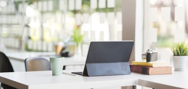 Geernteter schuss des modernen büroraumes mit tablette, kamera und büroartikel des leeren bildschirms
