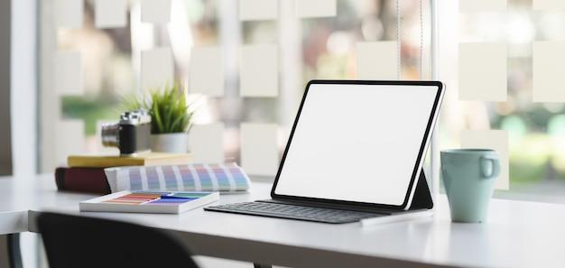 Geernteter schuss des modernen designerarbeitsplatzes mit tablette des leeren bildschirms auf weißem holztisch