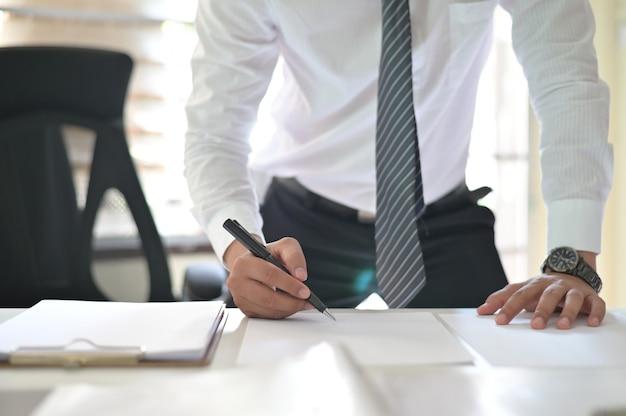 Geernteter schuss des unterzeichnenden vertrags des geschäftsmannes, der ein abkommen auf büroarbeitsplatz abschließt.