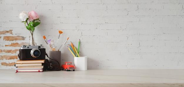 Geernteter schuss des weinlesearbeitsplatzes mit kamera und büroartikel auf marmortabelle und backsteinmauer