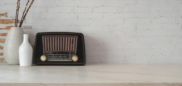 Geernteter schuss des weinlesearbeitsplatzes mit weinleseradio- und -vasendekorationen auf marmortabelle