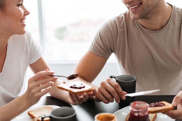 Geernteter schuss von den lächelnden paaren, die morgens frühstück essen