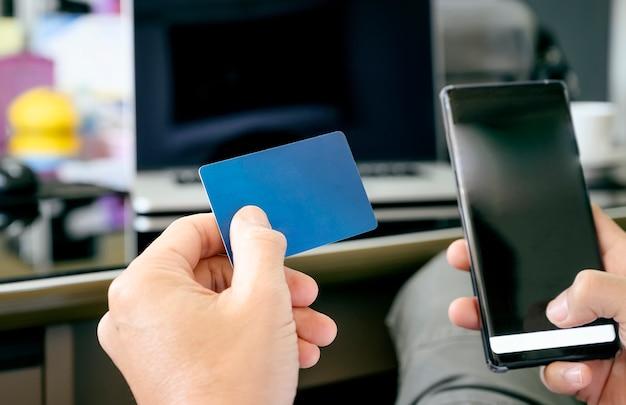 Geernteter schuss von den mannhänden, die blaue karte und smartphone zum online kaufen halten.