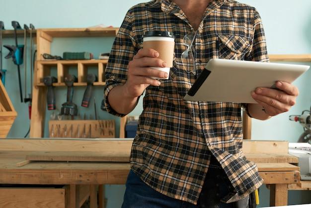 Geernteter tischler mit digitaler tablette und mitnehmerkaffee