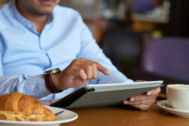 Geernteter unternehmensleiter, der drahtloses gerät in einem café verwendet