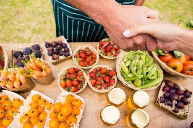 Geerntetes bild der frau hand mit dem mann rüttelnd, der früchte verkauft