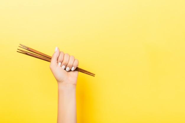 Geerntetes bild der weiblichen hand essstäbchen in der faust auf gelb halten