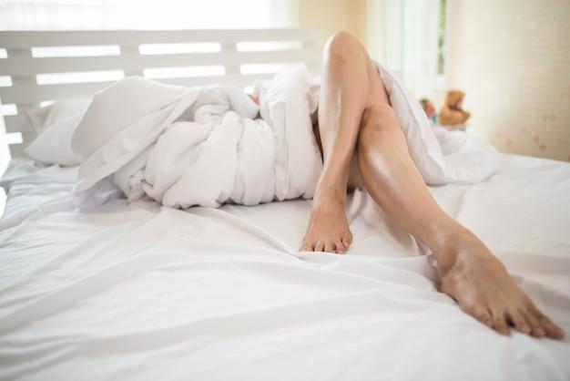 Geerntetes bild des beines liegend auf schöner frau des betts im schlafzimmer