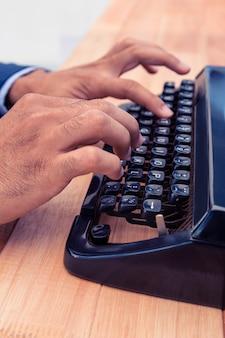 Geerntetes bild des geschäftsmannes schreibend auf schreibmaschine am hölzernen schreibtisch im büro
