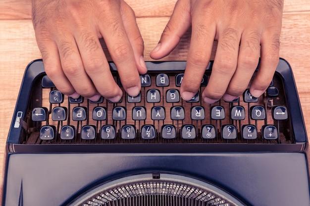 Geerntetes bild des geschäftsmannes schreibend auf schreibmaschine am schreibtisch im büro