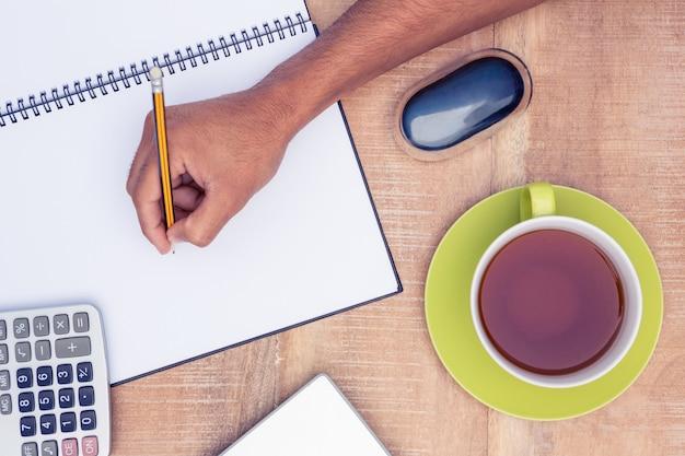 Geerntetes bild des geschäftsmannschreibens auf buch am schreibtisch im büro